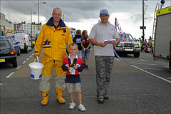 100801.064. Margate Lifeboat Crew. (actionsnaps) Tags: uk costumes boy male kent child stickers free lifestyle parade dressingup mohawk leisure shorts familyfun procession poloshirt flyers fancydress margate iro lifejacket waterbottle rubberboots drysuit lifevest lifesaver lifepreserver dayout rnli baseballcap maewest thanet familyevent leaflets publicevent communityevent protectiveclothing punkhairstyle royalnationallifeboatinstitution seaboots croppedhair landscapeformat personalfloatationdevice annualevent lifeboatcrew margatecarnival horizontalimage camouflagetrousers mohicanhaircut buoyancyaid collectionbucket openairentertainment adultslmen waterproofoutfit mustoyellowjacketandtrousers