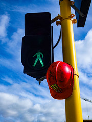 Go to Work (Steve Taylor (Photography)) Tags: trafficlight safety helmet pole green man walk red yellow blue art streetart strange odd weird metal plastic crane newzealand nz southisland canterbury christchurch cbd city summer cloud sky