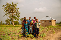 Farming Family Standing in Front of Their Home in Dodoma (IFPRI-IMAGES) Tags: tanzania hoe soil woman ifpri farm farmer work worker plot land crop field tilling till agriculture labor tend smallholderfarm familyfarm family community unit close group pose farmhouse ownership claim generations mother children girls matron female homestead womeninfarming womeninagriculture femalefarmers womenfarmers