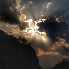 Cloudy Sun (Trips with Tripa) Tags: greece meteora clouds sun canyon mountains rays hills