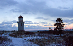 sunset at the lighthouse on the atlantic (Danny VB) Tags: ocean sunset sea sky cloud lighthouse snow seascape tree silhouette canon eos soleil coucher atlantic ciel neige nuage phare printemps lever