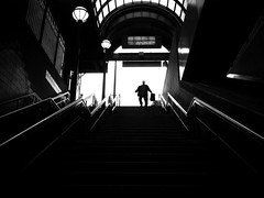 """Now boarding"" (Warfield360) Tags: street windows shadow sky urban man brick station silhouette sign architecture stairs train bag underground lights arch candid coat skylight running railings"