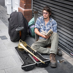 Trombone Player (James- Burke) Tags: ireland blackandwhite boy busker buskers candid casual colour dublin fuji fuji27mm instruments musician musicians pavement reading resting street streetcandid streetentertainer streetentertainers trombone player