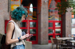 Colorfull (Streetphotography by Joost Smulders) Tags: streetphotography straatfotografie candid urban city stad rotterdam nederland holland mensen people vrouw woman girl hair blue graan color colour kleur kleurrijk colorfull phone telefoon rood red gebouw building terras