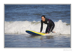 Happy Surfer (Seven_Wishes) Tags: newcastleupontynenortheast kc canoneos1dmarkiv canonef100400mmf4556lisii photoborder outdoor tynemouth longsands beach people candid coast surfer wetsuit femalesurfer surfboard sea water wet happy smile kneeling wave newcastleupontyne tyneandwear uk sport sunny