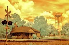 Andersonville Depot 3 (Neal3K) Tags: trees sky orange sunlight green clouds georgia ir watertower depot watertank andersonvillega infraredcamera rrtracks colorir vintagebuilding rrdepot rrsignal 590nmir kolarivisionmodifiedcamera