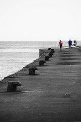 Walking on the pier (Mario Ottaviani Photography) Tags: sea people blackandwhite bw italy white seascape black monochrome walking grey monocromo pier mare sony gray bn tamron bianco nero molo biancoenero camminare gabicce sonyalpha