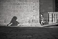 capita a tutti di rincorrere un'ombra (e_lisewin) Tags: bn biancoenero black white ombra shadow luce sera night montenegro kotor kotorbay cattaro piazza square plaza kid child illusioneottica optical correre run running gioco giocare play playful