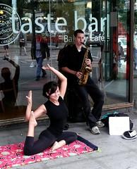 sax and yoga (D G H) Tags: daveheston downtown sax saxophone seattle streetphotography sidewalk street music musicians streetmusician urban man people yoga woman busker streetperformer