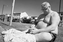 Protecting The Feet (nigelhunter) Tags: morecambe street sun bathe man torso glasses social media protect feet obese fat candid urban ipad tablet shorts