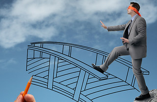 Businessman in a blindfold stepping off a cliff ledge with giant hand drawing a bridge for a safe cr