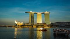 Golden Hour (elenaleong) Tags: sunset skyline architecture reflections singapore cityscape tourists goldenhour mbs lotusdesign bumboats helixbridge marinabaysands iconiclandmark artsciencemuseum