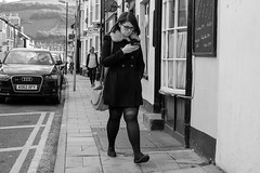 Expression (Photoblogger0069) Tags: road uk houses windows portrait people woman cars girl lines wall wales female walking glasses doors post serious pavement walk candid text cymru steps aberystwyth mobilephone casual ceredigion texting xf35mmf14r fujifilmxt1