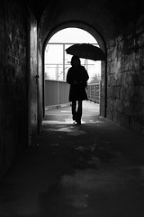0883 (.niraw) Tags: kln sdbrcke frau regenschirm regen bw niraw strasenfotografie gelnder stromleitung tunnel kontrast silhouette