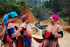 Hmong women at a market in Sapa (phuong.sg@gmail.com) Tags: travel red people woman black color tourism girl smile look lady hair asian person costume colorful asia vietnamese village dress market outdoor live traditional young tribal vietnam clothes souvenir stuff tradition suite tribe laos sell ethnic dao minority province sapa hmong headdress mong indochina insist