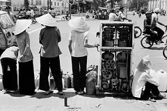SAIGON May 1975 (manhhai) Tags: white one s vietnam saigon photo|black white|full saigon|the back|turning seventies|communist regime|lack|shortage|fuel|gas|oil fuel|gasoline|gas|gas pump|woman|street scene|black back|horizontal