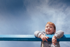 Young boy resting on play equipment (Robert Lang Photography) Tags: youngboyrestingonplayequipment ayoungchildrestshisarmsonblueplayequipmentonablueskybackground activity adventure blue boy child cloud copyspace face hand happy imagine male minimal outdoors outside play playground portrait redhair rest resting simple smile smiling sunshine thinking thought wonder youth robertlang robertlangphotography robertlangaustralia wwwrobertlangcomau