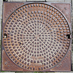 manhole cover, 2010 (doc(q)man) Tags: concentric cover lid sewer circle square iron metal surface abstract rhythm geometrics geometrical pavement tekst round numbers architecture rust oxydation rusty docman manholecover sewerlid castiron squaredcircle