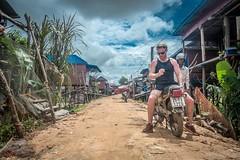 Traveller on a bike (sachasplasher) Tags: motorbike bike village cambodia asia poor poverty travel wander wonder clouds sky house helmet sunglasses backwards