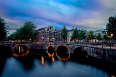 Turn on the lights (angheloflores) Tags: longexposure travel bridge houses sunset sky urban netherlands colors amsterdam architecture clouds reflections lights canal cityscape explore keizersgracht nihgt