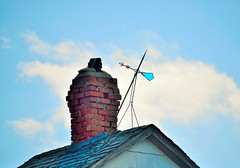 Hanging in there... (slammerking) Tags: blue roof chimney sky brick glass shingles bluesky fancy weathervane eaves