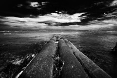 A storm coming (PhilPhotosity) Tags: old sky bw storm beach water mono horizon pipe pipeline beachmere