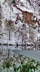 Winterly Tristesse at a Quarry Pond 01 (MJWoerner49) Tags: outdoor nature gloominess murkiness rees weather winter ice rocks structure surface reflection cold frosty winterly wintery wintry lake pond pool quarry quarrypond glacial icy
