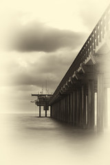 Vintage a-pier-ance -[ HSS ]- (Carbon Arc) Tags: sliderssunday pier sunset pacific ocean sea water surf nikcollection silverefexpro piles pillars sepia