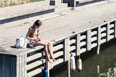 Sittin' on the dock of the bay (Jori Samonen) Tags: person woman sitting pier waterfront water kruununhaka helsinki finland