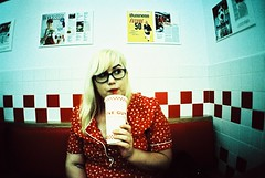 lc-a+sw - five guys chloe (johnnytakespictures) Tags: red food woman cute girl restaurant glasses lomo lca xpro lomography crossprocessed pretty fuji dress eating crossprocess fastfood chloe velvia fries burgers blonde teenager 20mm 50 fujichrome polkadot superwideangle fiveguys iso50 spectactles chloelee