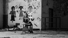 Nostalgia (Nate Conn) Tags: people monochrome light dark abandoned building urban decay exploring exploration urbex dress model girl woman teen teenager black white blackandwhite bw gray grayscale heels high big room painting elementary school wide field view aspect ratio desk sitting