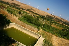 Nature and technology in diagonal. (Teteel) Tags: windgenerators ature green hill trees shrubbery southcrete greece  water
