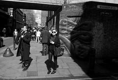 Soaking up the rays on Brick Lane (IanAWood) Tags: londonstreetphotography nikkorafs24mmf14g nikondf walkingwithmynikon lifeinbw lifeonthestreets ishootpeople urbancandid bricklane candid humansbeing