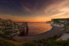 Sunset at Durdle Door (Pete 5D......) Tags: ocean door uk sunset sea england sky cliff reflection green beach water grass rock clouds evening coast chalk sand waves arch dusk cove south horizon hill wave landmark cliffs formation dorset coastline durdle durdledoor