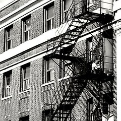 Escaping Summer heat on the escape (williamw60640) Tags: door windows summer chicago man hot brick alley streetphotography sunny uptown sit heat fireescape cityscenes wilsonave masonrybuilding
