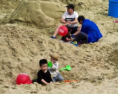 Sitting in the Sand (Mondmann) Tags: sitting sand beach shore haeundaebeach haeundae busan pusan korean southkorea rok republicofkorea asia eastasia koreans children boys girl men kids recreation korea digging mondmann canonpowershotg7x