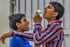 Beating the heat (Aiel) Tags: friends summer india boys water up arms drink drinking shoulders allahabad packets uttarpradesh canon60d tamron70300vc