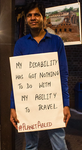 My disability doesn't stop my wanderlust: One of our travellers with a poster, which says. 'My disability has got nothing to do with my ability to travel'.
