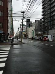 Street Scene in Sapporo (sjrankin) Tags: 19july2016 edited hokkaido sapporo japan street overcast drizzle crosswalk lines buildings cars