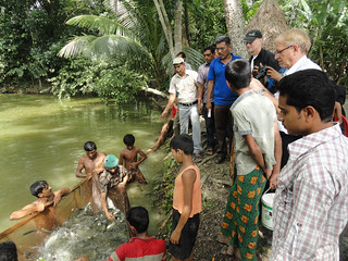 Director General of WorldFish, Dr. Stephen Hall (wearing a cap) visits a successful carp nursery in Barisal, Bangladesh where improved fish seeds and skills changed the business of fish farmer Mosaref.