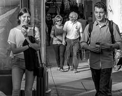 The Future is Catching Up. (Szoki Adams) Tags: street blackandwhite bw coffee monochrome smile sunshine sunglasses smiling standing canon walking happy montreal smiles streetphotography jeans jacket shade streetphoto chic rucksack talking relaxed youngcouple graceful youngman oldercouple sunnyday younggirl beautifulgirl streetphotos svelte squinting atease blackwhitephotos sherbrookestreet szoki canong15 szokiadams
