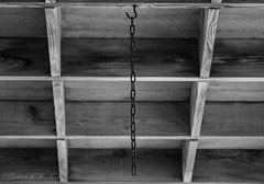The Rusted Chain (Gabriel FW Koch) Tags: chain wood squares perspective bw telephoto lseries eos dof canon bokeh outdoor outside ceiling