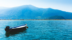 Lonely boat (Nicola Pezzoli) Tags: blue people italy mountain lake art tourism nature water colors yellow canon reflections island design boat piers floating monte bergamo brescia lombardia isola iseo sulzano