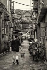 A Woman Walking in the Alley with a Bucket (Shinichiro Hamazaki) Tags: china woman bucket alley shanghai