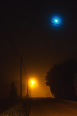 Crescent in the mist (Lux Obscura) Tags: fog mooncrescent orange blue home houses trees road public light pollution mist wires poles night