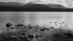 if stones could tell us their stories (lunaryuna (travelling for a week)) Tags: scotland cairngorms northerncairngorms nationalpark lochmorlich lake landscape mountains shore water rocks sky reflections le longexposure blackwhite bw monochrome lunaryuna
