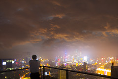 Young man lookin the night  of Shanghai city in a foggy night,shot by tilt and shift lens (Olivier Dantiq) Tags: china street city travel blue sky people urban man building tower tourism fog skyline architecture modern night skyscraper standing river lights office construction asia downtown cityscape looking view shanghai traffic dusk district famous chinese young foggy landmark center scene panoramic structure dirty business metropolis pudong financial development bund futuristic prosperity finance polluted lujiazui huangpuriver suzhouriver