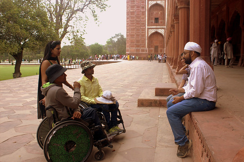 Our heritage expert telling stories of Taj Mahal. He is sitting on a porch with another team member of Planet Abled. Two travellers on wheelchairs with hats on, along with a girl traveller listen carefully. The backdrop is a red sandstone monument.