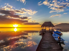 PIER SUNSET (In Explore Jul 16, 2016) (robbiedest) Tags: travel sunset orange sun lake color reflection clouds landscape boats pier guatemala waterscape peten