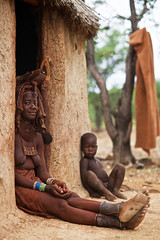 Himba mother with her child, Kaokoland, Namibia (Alex_Saurel) Tags: africa door people woman color wall architecture female pose cabin day sitting village adult arm outdoor body african femme traditional leg culture photojournalism posing tribal case doorway hut portraiture shanty nomad porte tradition tribe ethnic indigenous doorframe afrique africans lifestyles hutte tribu nomadic southernafrica crosslegged portray fullbody ethnique ethnie afriqueaustrale planitalien nomadicculture 85mmf14za planpied nomadicherder indigène nomadicherderculture